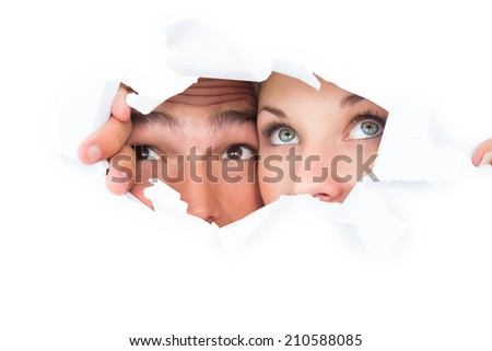 Young couple peeking through torn paper on white background