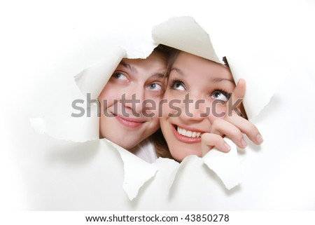 young couple peeping through hole in white paper - stock photo