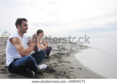young couple people meditating yoga in lotus position at early morning on the beach - stock photo