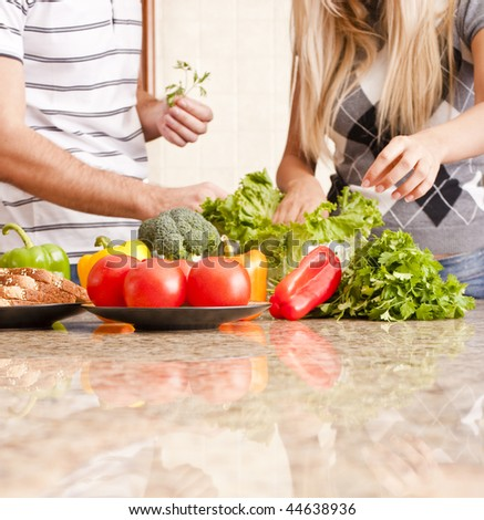Young couple pick through fresh vegetables behind a kitchen counter. Square shot. - stock photo