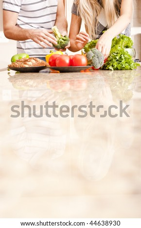 Young couple picks through fresh vegetables at the far end of a kitchen counter. Vertical shot. - stock photo