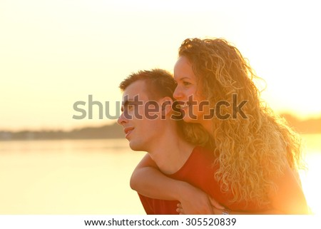 young couple piggyback beside a lake at sunset - stock photo