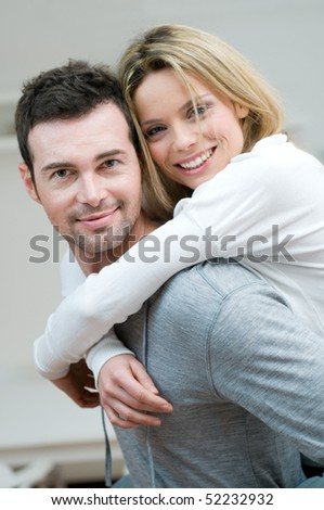 Young couple piggybacking and have fun at home - stock photo