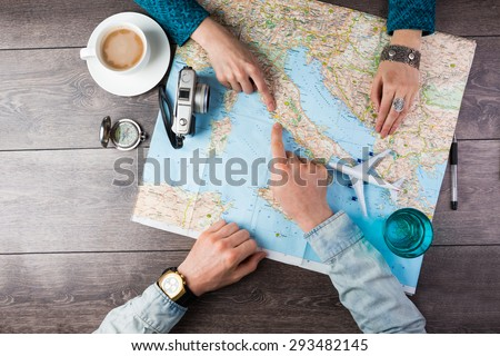 Young couple planning honeymoon vacation trip with map. Top view. Pointing to Europe Rome - stock photo
