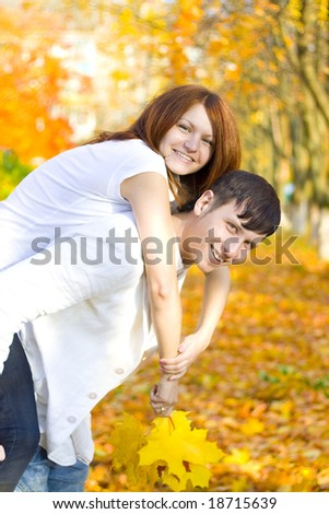 young couple play piggyback in autumn park - stock photo