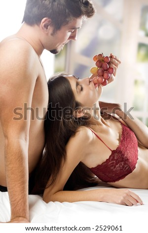 Young couple playfully eating grapes on the bed in bedroom - stock photo