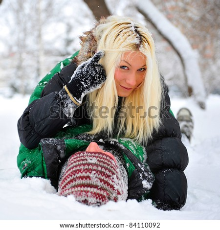 Young couple playing around in the nature in winter park. Laying on the snow and embracing - stock photo