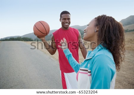 Young couple playing around with basketball - stock photo