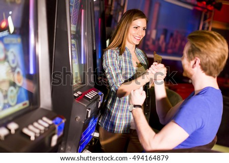 Young couple playing at slot machine in the casino