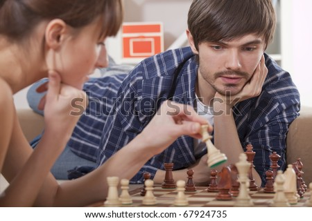young couple playing chess game at home - stock photo