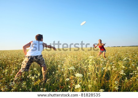 Young couple playing frisbee on a green meadow with grass on clear blue sky background - stock photo