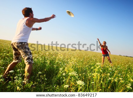 Young couple playing frisbee on a green meadow with grass on clear blue sky background. Focus on a woman, man is motion blurred