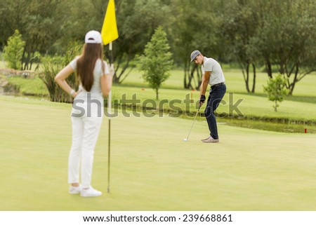 Young couple playing golf - stock photo