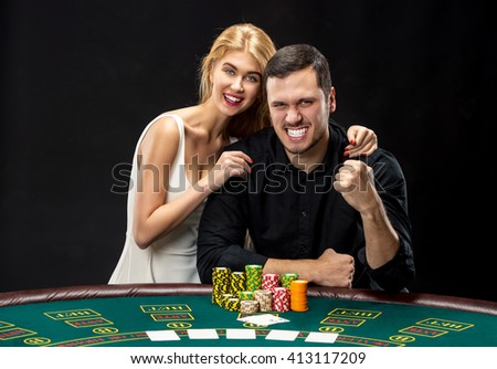 Young couple playing poker have a good time in casino - stock photo