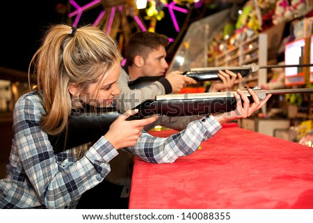Young couple playing shooting games while visiting an amusement park arcade at night time, having fun with color lights and rides in the background. - stock photo