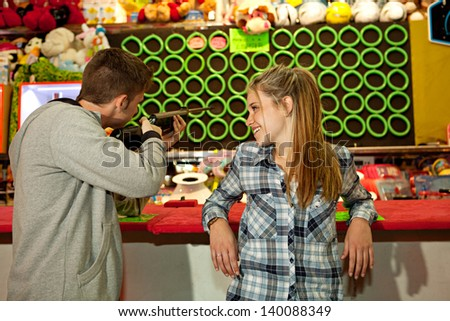 Young couple playing shooting games while visiting an amusement park arcade at night time together, having fun and competing, with prizes in the background - stock photo