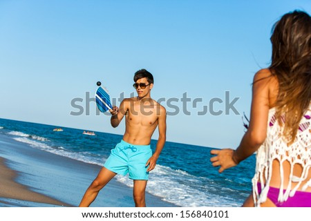 Young couple playing smash ball beach tennis outdoors.