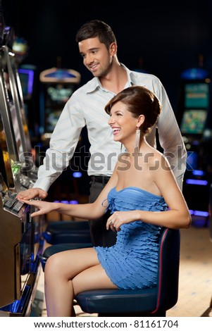 young couple playing together at slot machine - stock photo