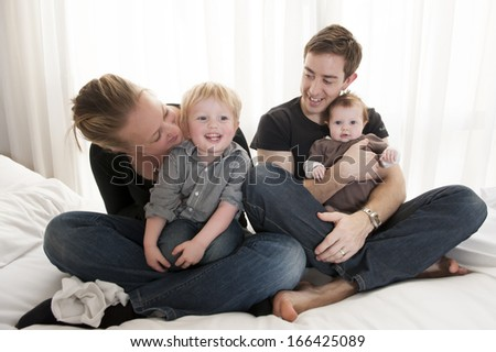 Young couple playing with baby girl and little child sitting
