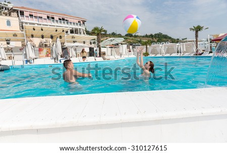 Young Couple Playing with Beach Ball in the Swimming Pool on a Tropical Climate. - stock photo