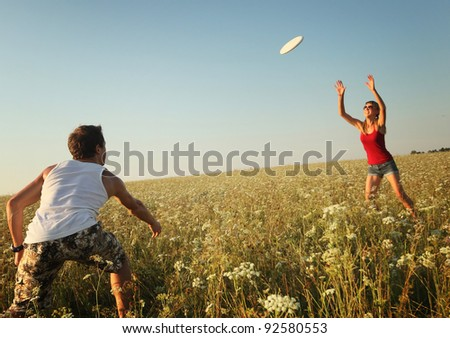 Young couple playing with disc on a green meadow with grass on clear blue sky background. Focus on the man - stock photo