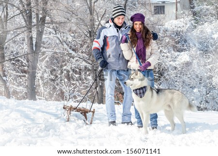Young couple playing with his dog in snowy forest - stock photo