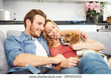 Young Couple Playing With Pet Dog At Home - stock photo