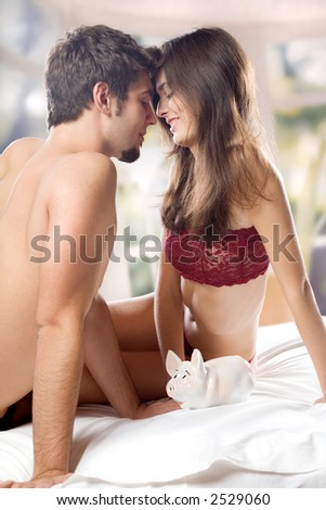 Young couple playing with piggy bank on the bed in bedroom - stock photo