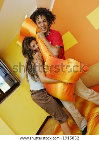young couple playing with pillows - stock photo