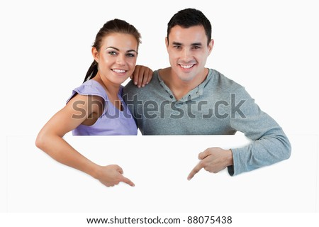 Young couple pointing at advertisement below them against a white background - stock photo