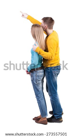 young couple pointing at wal Back view  (woman and man). Rear view people collection.   The guy in the yellow sweater hugging behind her and shows her something interesting in the sky. - stock photo