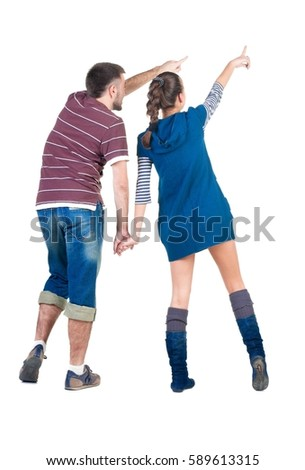 young couple pointing at white wall . Rear view .