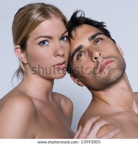 young couple portrait naked in studio on isolated grey background - stock photo