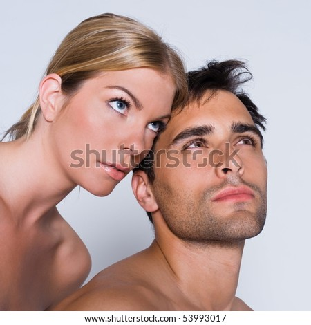 young couple portrait thinking naked in studio on isolated grey background - stock photo