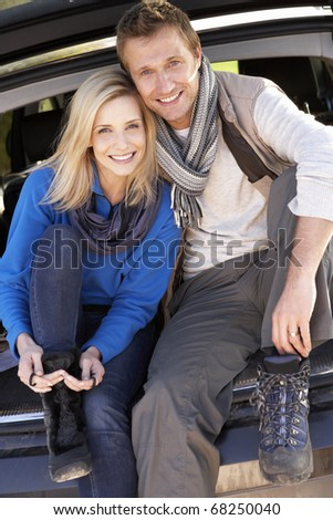 Young couple pose together at rear of car - stock photo