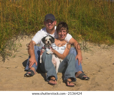 Young couple pose with their dog on the beach - stock photo