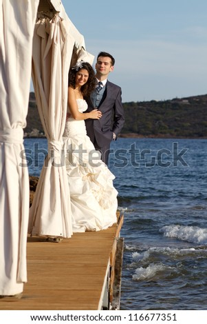 Young couple posing at the sea after their wedding ceremony - stock photo