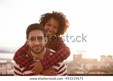 Young couple posing for a fun picture while he is piggy backing her and they are both smiling very happily