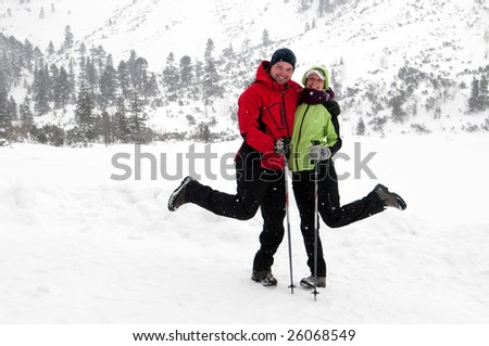 young couple posing having fun in the snow covered country - stock photo