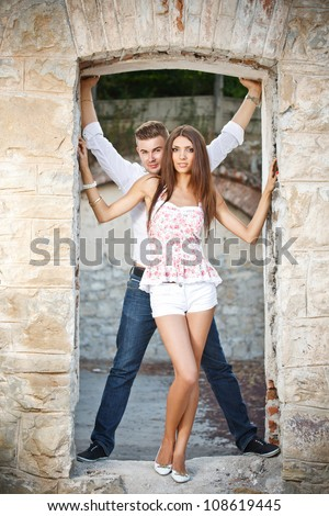 Young couple posing in a ruined building - stock photo