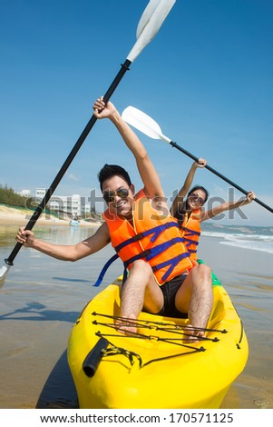 Young couple posing in kayak with oars - stock photo