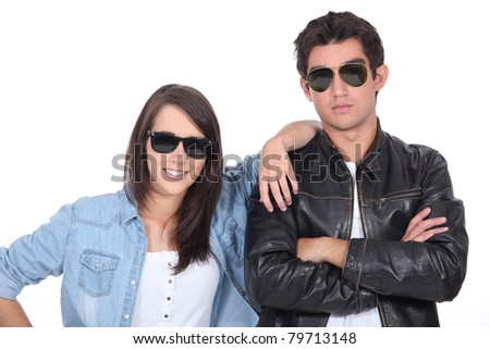 Young couple posing in sunglasses and leather jacket - stock photo