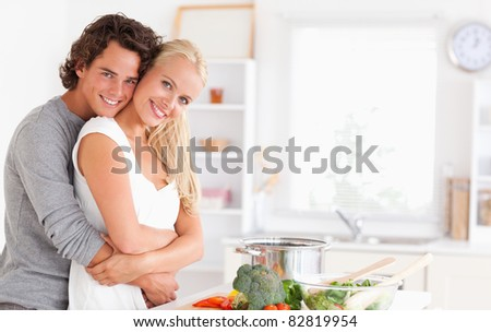 Young couple posing in their kitchen - stock photo
