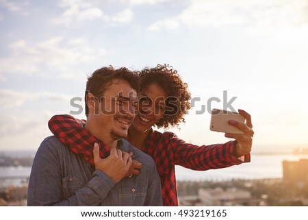 Young couple posing joyously for a selfie while holding each other lovingly with toothy smiles