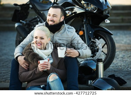Young couple posing near motor bike with sandwitches and coffee and smiling - stock photo