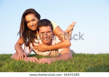 Young couple posing on a field - stock photo