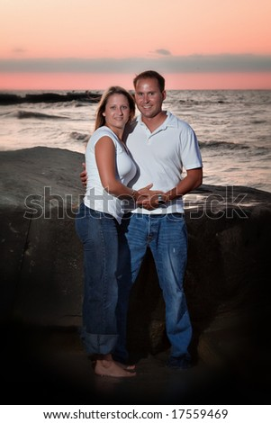 Young couple posing on beach at sunset.