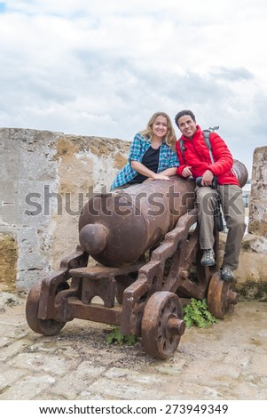 Young couple posing on old cannon in El Jadida, Morocco - stock photo