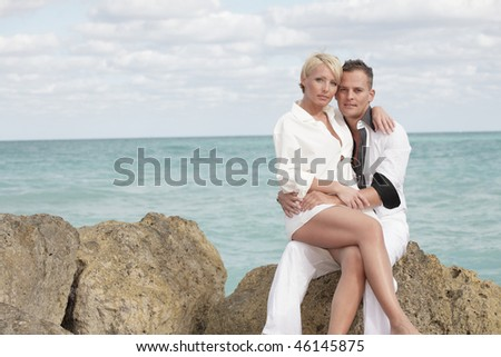 Young couple posing on the beach rocks