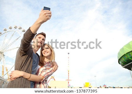 Young couple posing together at an attractions park arcade and using their smartphone to take a picture of themselves smiling. - stock photo